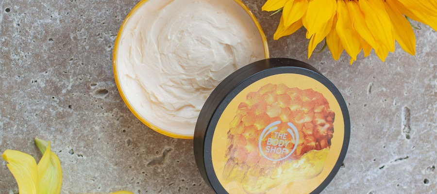 body shop body butter flatlay with sunflower and lilly